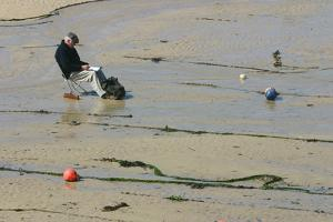 Man sitting on the sand in St Ives harbour at low tide, Cornwall by Peter Thompson