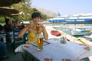 Woman Enjoying a Drink in a Harbourside Taverna, Poros, Kefalonia, Greece by Peter Thompson
