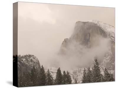 Half Dome Stands Amid the Clouds in Yosemite Valley in Winter