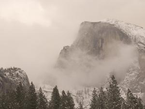 Half Dome Stands Amid the Clouds in Yosemite Valley in Winter by Phil Schermeister