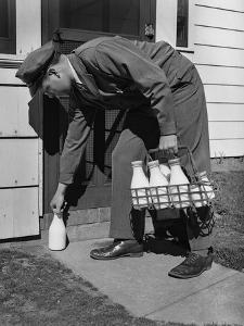 Milkman Leaving Milk Bottle on Doorstep by Philip Gendreau