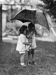 Two Children under Umbrella During a Downpour by Philip Gendreau