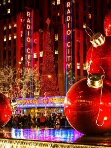 The Giant Christmas Ornaments on Sixth Avenue across from the Radio City Music Hall by Night by Philippe Hugonnard