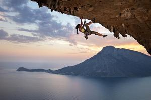 Young Female Rock Climber at Sunset, Kalymnos Island, Greece by photobac