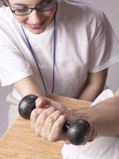 Physical Therapist Assisting Patient in Using Free Weight--Photographic Print