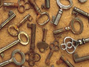 Pile of Antique Keys on Wood Table