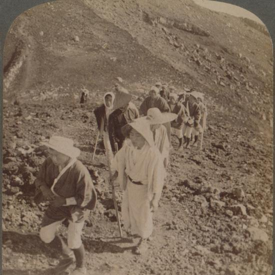 'Pilgrims, at end of weary ascent, in worship encircling crater of sacred Fujiyama, Japan', 1904-Unknown-Photographic Print