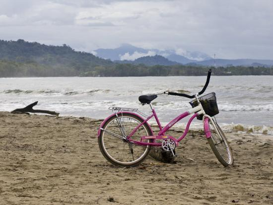 Pink Bike Sits on the Beach in Cahuita National Park-Hannele Lahti-Photographic Print