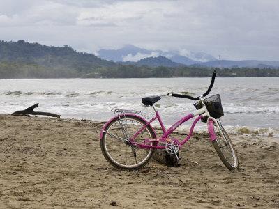 https://imgc.artprintimages.com/img/print/pink-bike-sits-on-the-beach-in-cahuita-national-park_u-l-p8g6mt0.jpg?p=0