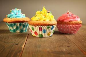 Three Different Colors Cupcakes On A Wooden Table, Blue, Yellow And Pink by pink candy