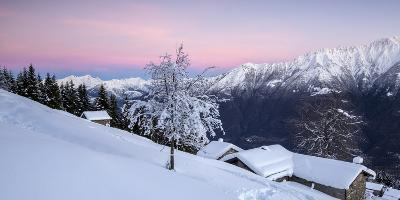 Pink Sky at Dawn Above Snow Covered Huts and Trees, Orobie Alps-Roberto Moiola-Photographic Print