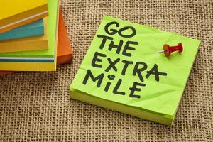 Go the Extra Mile - Motivational Reminder or Procrastination Concept - Handwriting on Sticky Note by PixelsAway
