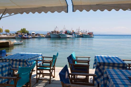 Platanias, Thessaly, Greece. Tables and chairs outside a harbour side restaurant. Fishing boats...--Photographic Print