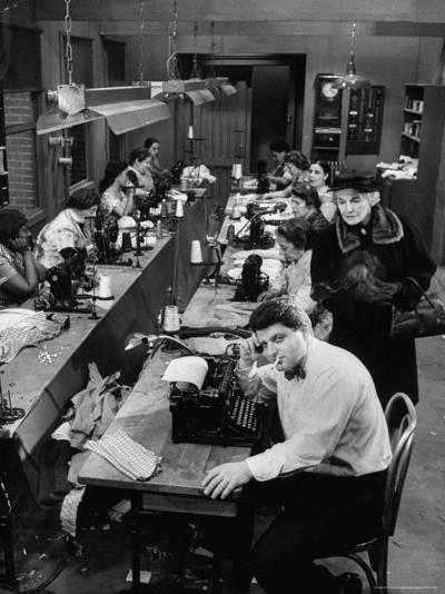 Playwright Paddy Chayefsky Sitting at Typewriter in Garment Factory With Workers on Sewing Machines-Michael Rougier-Premium Photographic Print
