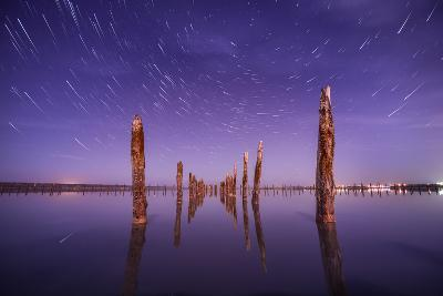 Poles in the Water at Night on a Background Star Trails- Q-lieb-in-Photographic Print