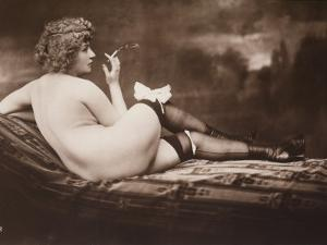 Portrait of a Young Woman Posing Naked, with Her Back Turned, as She Smokes a Cigarette