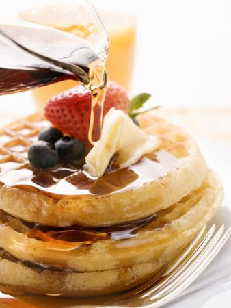 Pouring Maple Syrup over Waffles with Butter and Berries