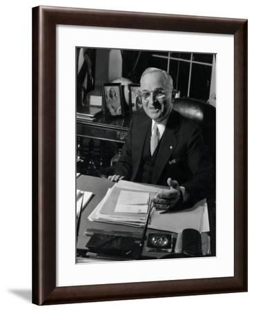 Pres. Harry S. Truman Seated at His Desk in the White House, Family Photographs on Table Behind Him-Gjon Mili-Framed Photographic Print