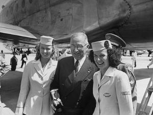 President Harry S. Truman Standing Near a Plane Flanked by Stewardesses