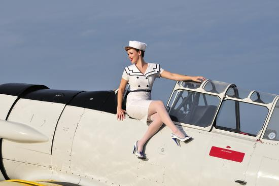 1940-s-style-pin-up-girl-sitting-outside-the-cockpot-of-a-t-6-texan