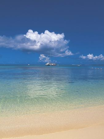 a-beach-with-the-blue-ocean-and-sky-with-white-clouds