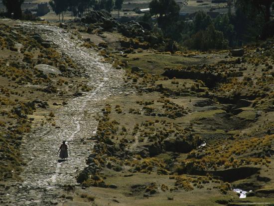 a-bolivian-woman-walks-along-the-ancient-road-to-tiwanaku