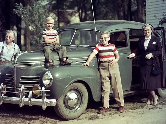 a-family-poses-on-and-around-their-plymouth-automobile-ca-1953