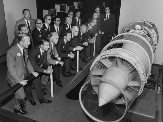 a-group-of-men-in-suits-looking-at-a-jet-engine-on-display-at-museum-of-science-and-industry