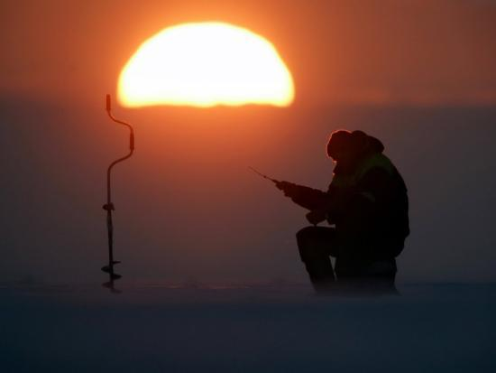 a-man-icefishes-on-the-frozen-finnish-gulf-at-sunset-outside-st-petersburg