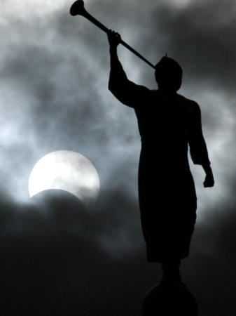 a-statue-is-seen-against-a-cloudy-sky-and-a-partial-solar-eclipse