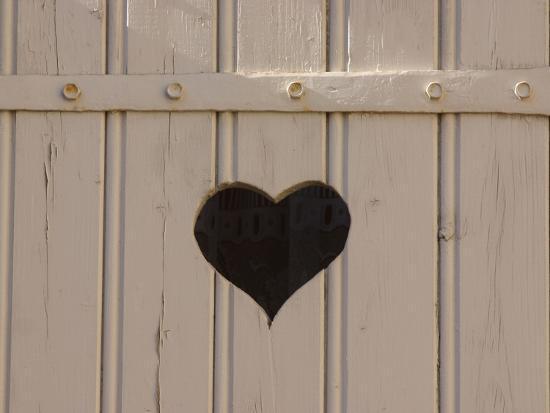 a-white-picket-fence-with-a-black-heart-cut-out