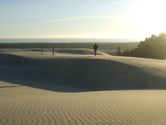 aaron-mccoy-woman-walking-barefoot-on-sand-dunes-torwards-the-pacific-ocean-southern-oregon-usa