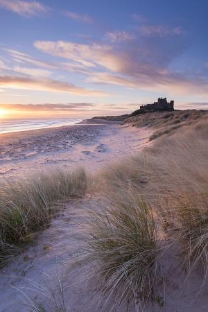 adam-burton-sunrise-over-bamburgh-beach-and-castle-from-the-sand-dunes-northumberland-england-spring-march