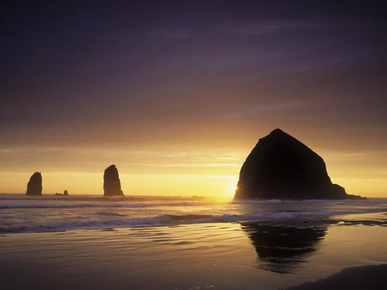 adam-jones-haystack-rock-and-other-sea-stacks-silhouetted-at-sunset-cannon-beach-oregon-usa