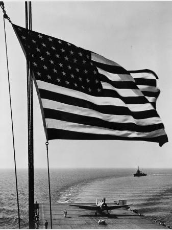 airplane-on-battleship-deck-with-american-flag-in-foreground-world-war-ii