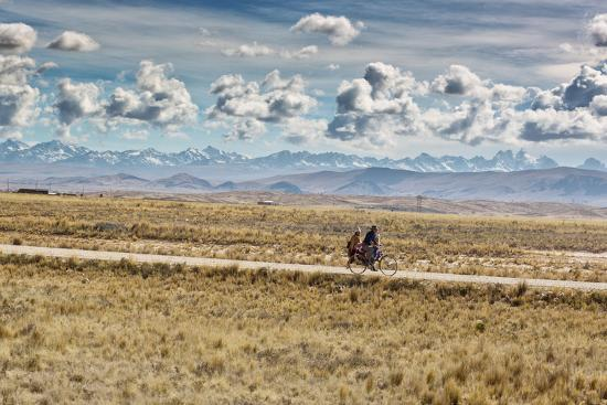alex-saberi-a-man-cycles-with-a-family-member-on-the-back-of-his-bicycle-between-la-paz-and-tiwanaku