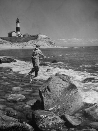alfred-eisenstaedt-man-fishing-off-montauk-point-montauk-lighthouse-visible-in-background