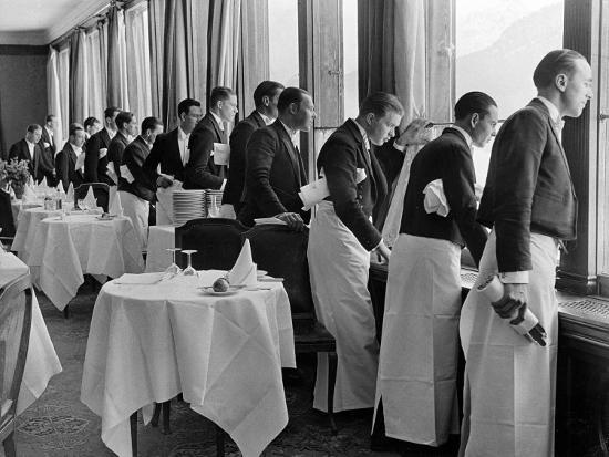 alfred-eisenstaedt-waiters-in-the-grand-hotel-dining-room-lined-up-at-window-watching-sonia-henie-ice-skating-outside