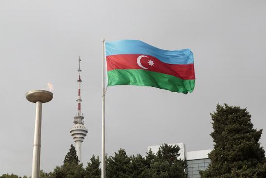 alida-latham-azerbaijan-baku-an-azerbaijan-flag-waves-near-a-memorial-flame-and-the-baku-tv-tower
