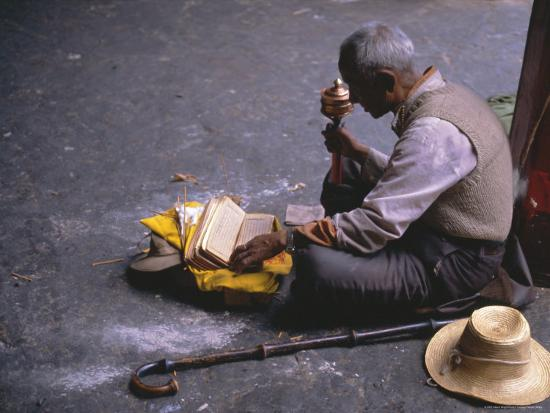 alison-wright-tibetan-buddhist-pilgrim-reading-texts-and-holding-prayer-wheel-lhasa-china
