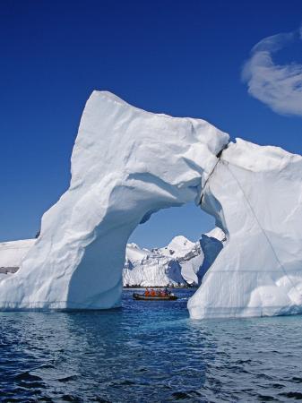 allan-white-grandidier-channel-tourists-zodiac-cruising-by-arched-iceberg-near-booth-island-antarctica