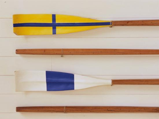 an-array-of-boat-oars-mounted-on-a-wall