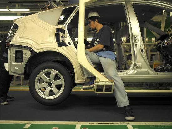 an-auto-worker-assembling-a-hybrid-car-at-plant-in-japan