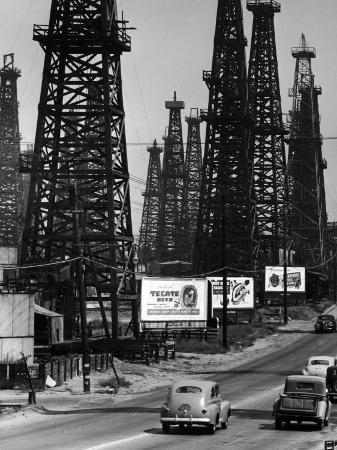 andreas-feininger-car-traffic-on-highway-next-to-advertising-billboards-and-oil-well-towers-signal-hill-oil-field