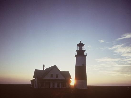 andreas-feininger-golden-sunset-at-nantucket-mass-with-sankaty-head-lighthouse-silhouetted-against-sky
