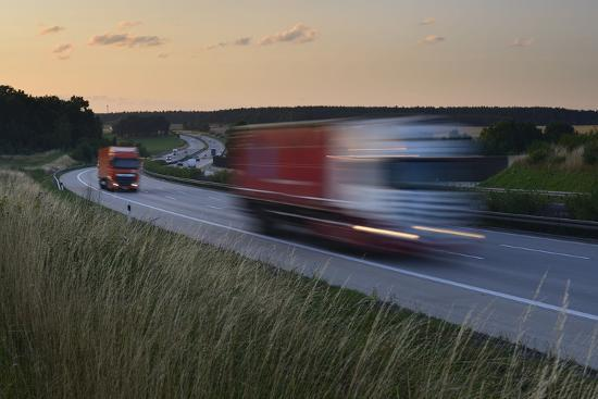 andreas-vitting-germany-thuringia-highway-a9-close-lederhose-truck-and-car-in-motion-blur-at-sundown