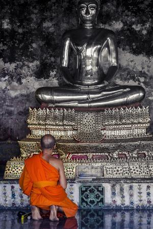 andrew-taylor-a-monk-prays-in-front-of-a-golden-buddha-wat-suthat-bangkok-thailand-southeast-asia-asia