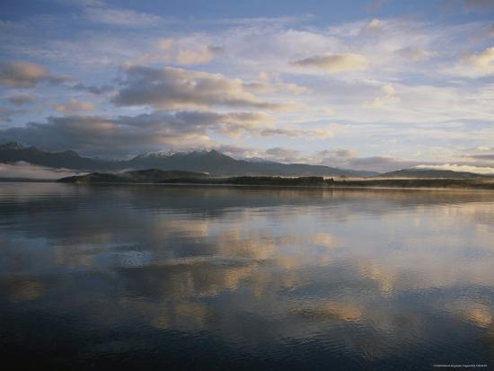annie-griffiths-clouds-and-shoreline-reflected-in-tranquil-waters-at-sunset