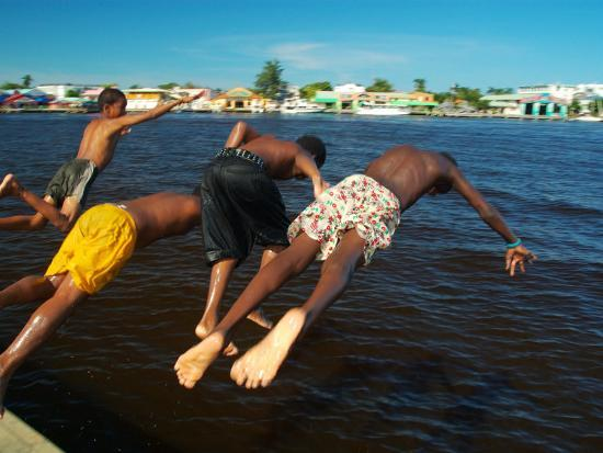anthony-plummer-young-boys-dive-off-marina-at-bay-of-belize-with-city-in-background-belize-city-belize