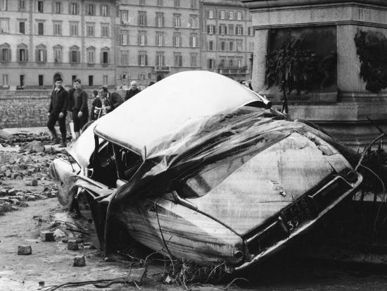 automobile-destroyed-and-flung-up-against-a-monument-during-the-flood-in-florence